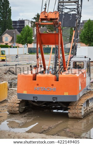 STRASBOURG, FRANCE - MAY 15, 2016: HITACHI excavator in a puddle on a construction site waiting to perate - stock photo