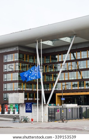 STRASBOURG, FRANCE - 14 Nov 2015: European Union Flag flies at half-mast in front of the Counci lof Europe building, Agora - following an terrorist attack in Paris - stock photo