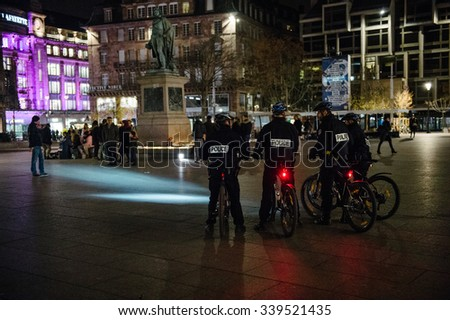 STRASBOURG, FRANCE - 14 NOV 2015: Police officers on bike looking at people and candles during a vigil in the center of Strasbourg for the victims of the November 13 attacks in Paris - stock photo