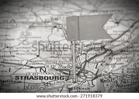 Strasbourg, France. Red flag pin on an old map showing travel destination. Black and white toned image. - stock photo