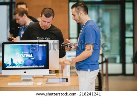 STRASBOURG, FRANCE - SEPTEMBER 19, 2014: An Apple Inc. genius employee assists a customer with the purchase during the sales launch of the iPhone 6 and iPhone 6 Plus - stock photo