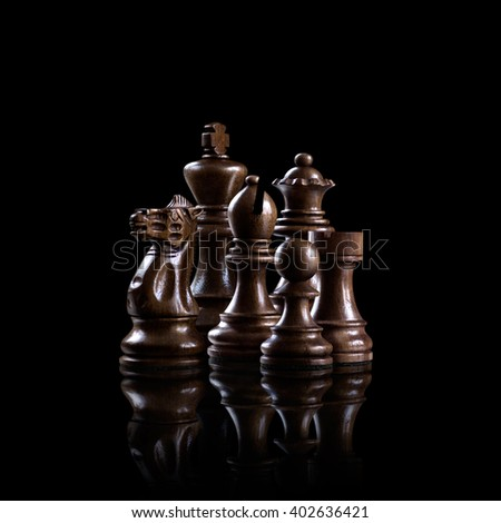 Strategy and leadership concept; black wooden chess figures standing together as a family ready for game against dark background. - stock photo