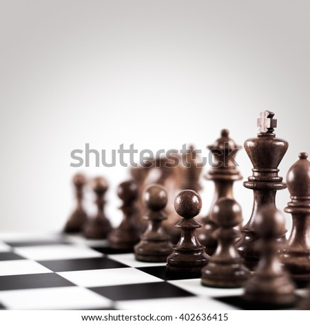 Strategy and tactics concept; black wooden chess figures on the board standing in a row ready for game. - stock photo