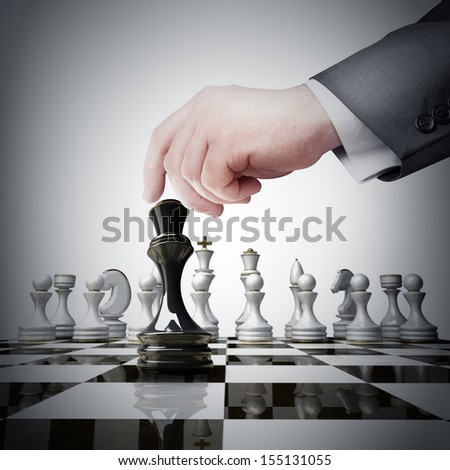 Strategy concept. hand holding black chess figure on chess board  - stock photo
