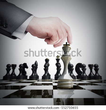 Strategy concept. hand holding white chess figure on chess board  - stock photo
