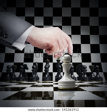 Strategy concept. hand holding white chess Pawn on chess board - stock photo