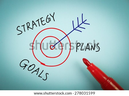 Strategy concept is on blue paper with a red marker aside. - stock photo