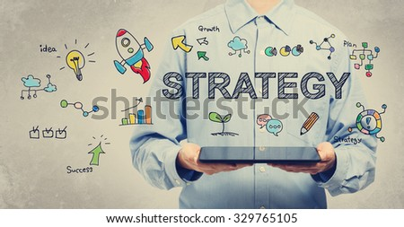 Strategy concept with young man holding a tablet computer  - stock photo