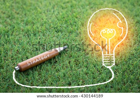 strategy ideas woth pencil and bulb drawing on green field with copy-space for your idea - stock photo