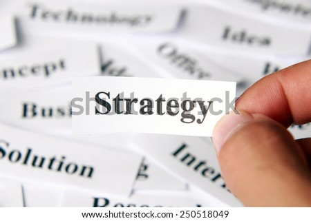 Strategy word paper in hand with the background of other words.