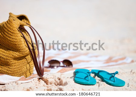 Straw bag, sun glasses, towel and flip flops on a tropical beach  - stock photo