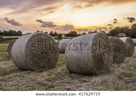 Straw bale in sunset on a farm at the countryside. - stock photo