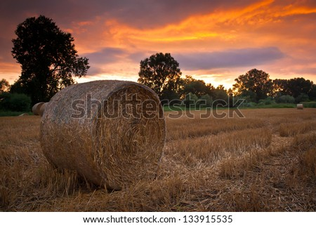 Straw bale on the stubble in breathtakingly beautiful sunset - stock photo