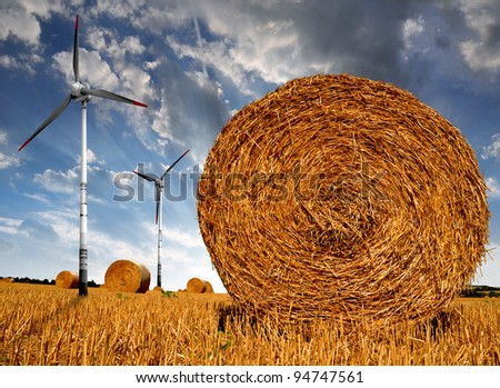 Straw bales on farmland with wind turbine in the sunset - stock photo