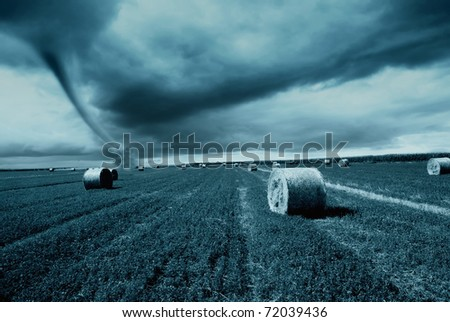 straw bales under cloudy sky with twister - stock photo