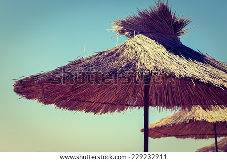 Straw beach umbrella on a background of the cloudless sky. - stock photo