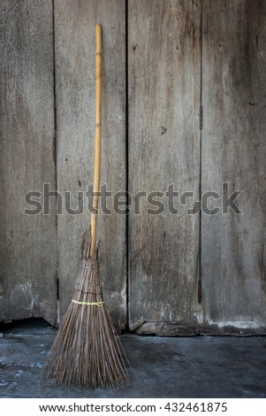 Straw broomstick on wood wall - stock photo