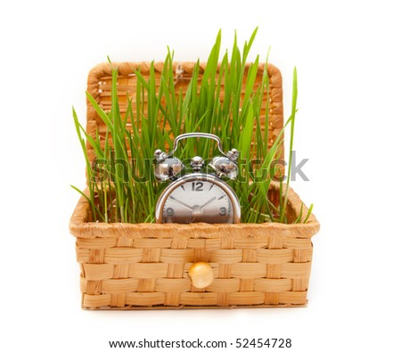 Straw casket with a green grass of wheat and hours - stock photo
