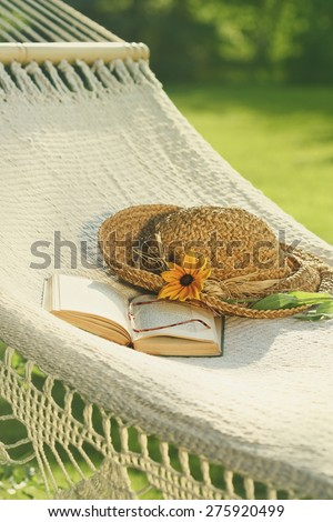 Straw hat and book on lace hammock - stock photo