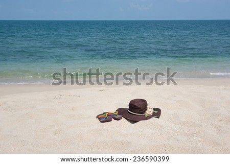 Straw hat and flip flops on sandy beach