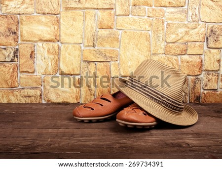 Straw hat and moccasins on a wooden table in front of a stone wall. Toned.