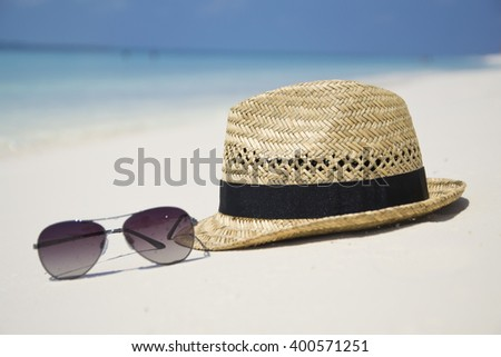 Straw hat and sun glasses on a paradise tropical beach with turquoise sea, Kuredu, Maldives - stock photo