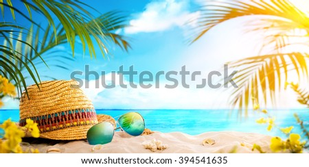 Straw hat and sun glasses on beach - stock photo
