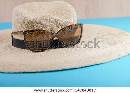 Straw hat and sunglasses on blue background. beach equipment.
