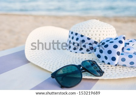Straw hat and sunglasses on the beach - stock photo