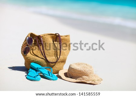 Straw hat, bag, sun glasses and flip flops on a tropical beach - stock photo