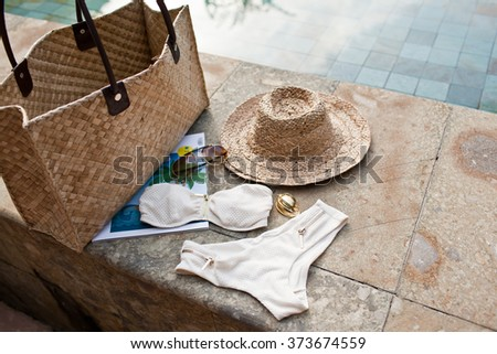 Straw Hat Bag Sunglass White Womans Swimsuit and Landscape of Summer Swimming Pool - stock photo