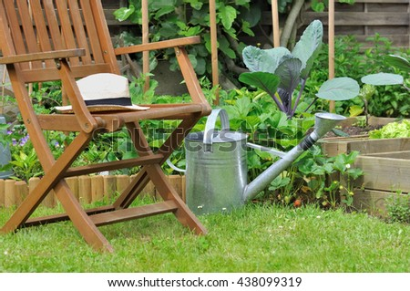 straw hat on a wooden chair in garden - stock photo