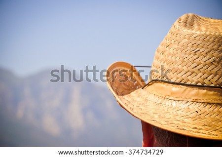 Straw hat on head and the sky and mountains far away - stock photo