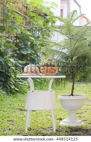 Straw hat on white table in the garden