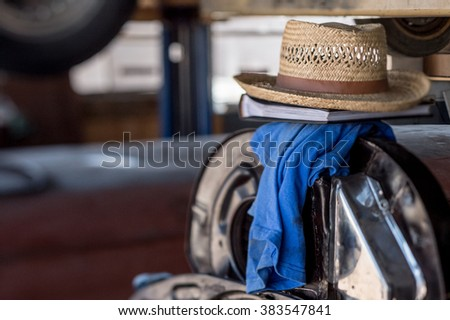 Straw hat resting in workplace with blurred background - stock photo