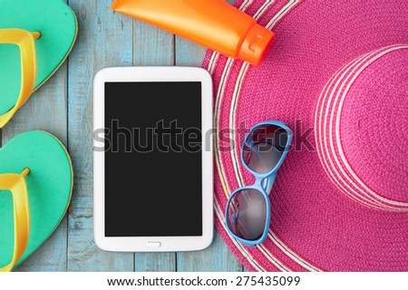 Straw hat tablet and sunglasses on blue wood.Summer holiday background concept - stock photo