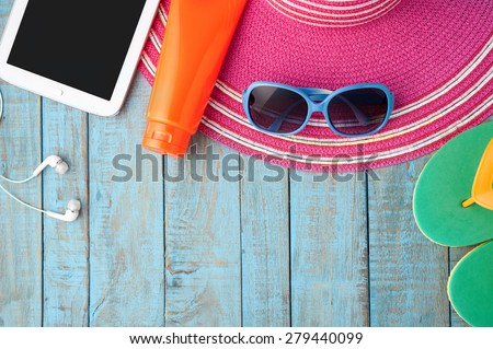 Straw hat tablet and sunglasses on blue wood.Summer holiday background concept.Copy Space - stock photo