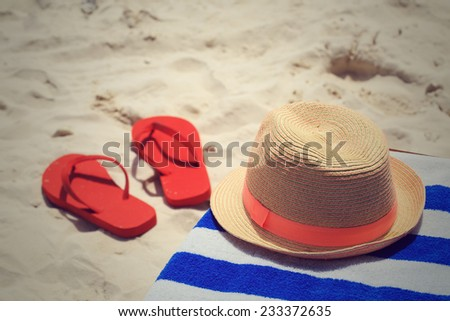 Straw hat, towel and flip flops on tropical sand beach - stock photo