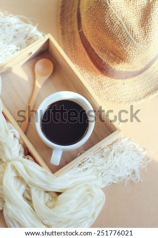 Straw hat with black coffee and spoon on wooden tray, retro filter effect - stock photo