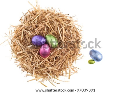 Straw nest with chocolate Easter eggs over white studio shoot - stock photo