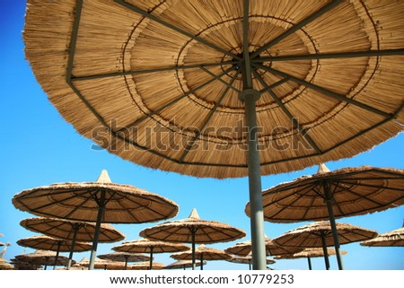 straw parasols on beach on blue sky background - stock photo