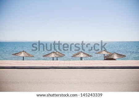 straw sun umbrellas at the beach, road and sea visible - stock photo