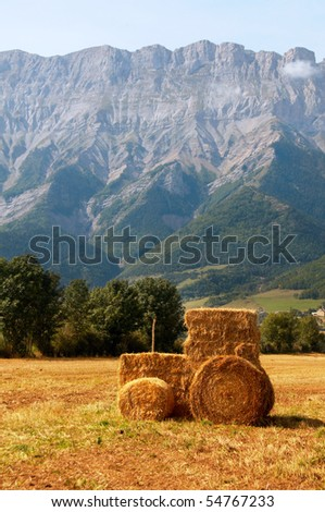 Straw Tractor in a field against a mountain - stock photo