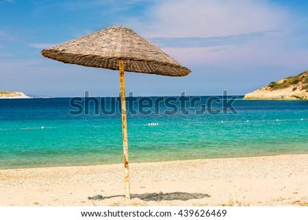 Straw umbrella in a sandy beaches of Kusadasi Region in Aegean Sea coastline of Turkey - stock photo