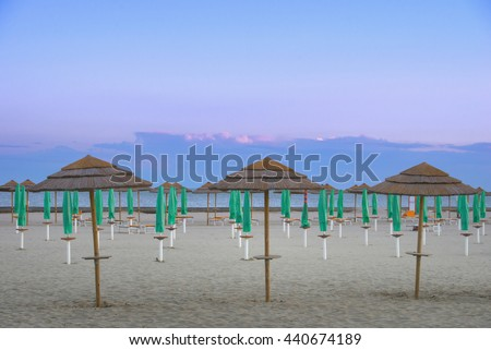 straw umbrella in the foreground, in the background other umbrellas, empty beach