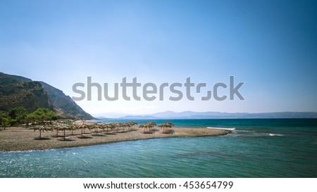 Straw umbrella on a sandy beach in Greece. Beach chairs with umbrellas on a beautiful beach in Crete island. - stock photo
