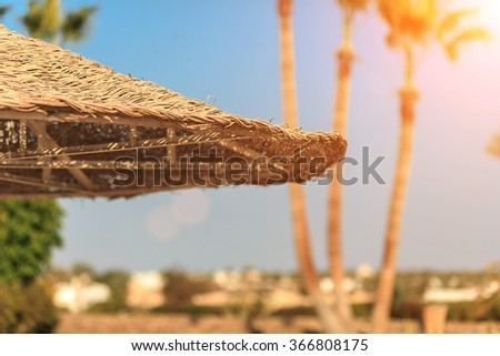 Straw umbrellas against the sky with view at palm trees - stock photo