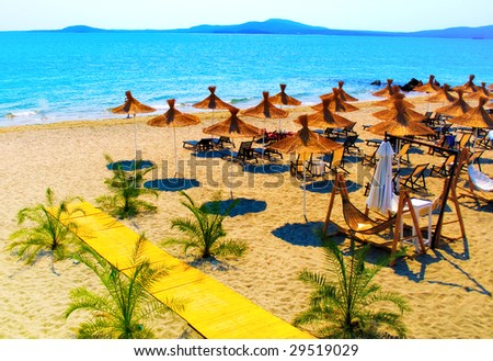 Straw umbrellas on beautiful sunny beach in Bulgaria - stock photo