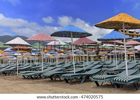 Straw umbrellas with chairs on beach in Turkey