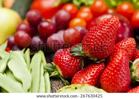 Strawberries among other fruits and vegetables - stock photo